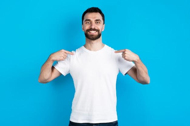 Hombre posando mientras se señala a sí mismo Foto gratis