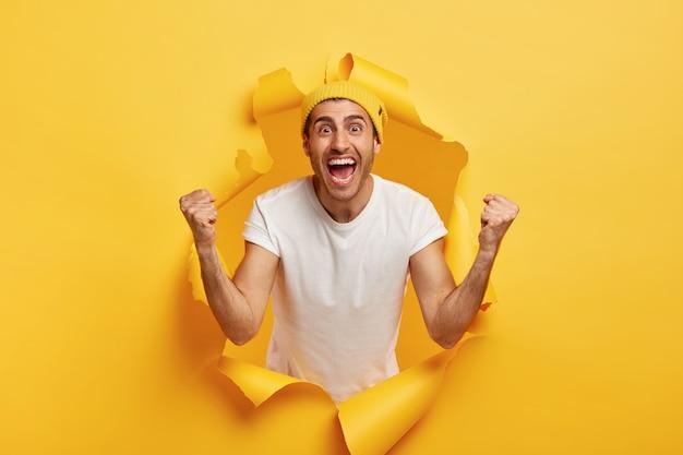 El hombre positivo aplaude con los puños cerrados, celebra la victoria, viste una camiseta blanca informal y un sombrero amarillo Foto gratis