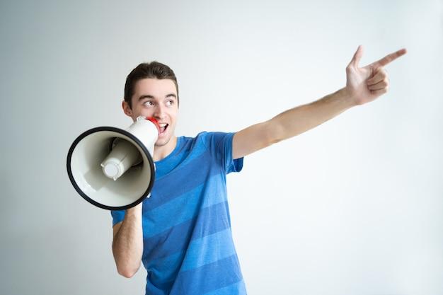 Hombre positivo hablando en megáfono y apuntando a un lado Foto gratis