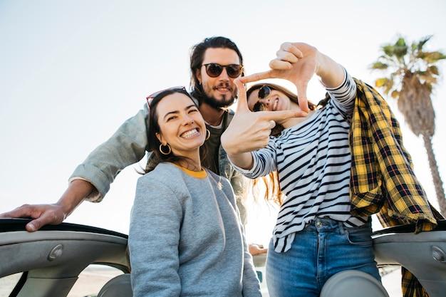 Hombre positivo y mujeres sonrientes haciendo marco, divirtiéndose e inclinándose hacia fuera del auto Foto gratis