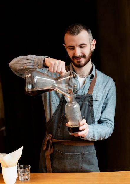Hombre preparando café para clientes Foto gratis