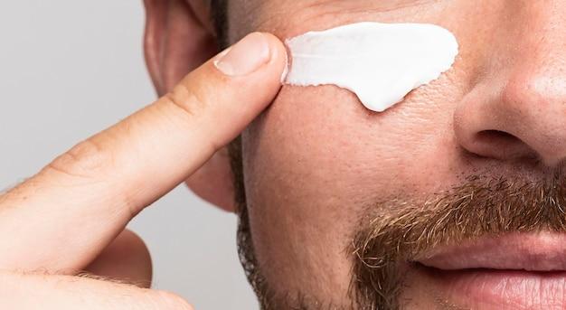 Hombre con primer plano de crema facial Foto gratis