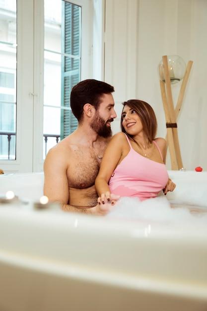 Hombre que abraza a la mujer sonriente en tina del balneario con agua y espuma Foto gratis