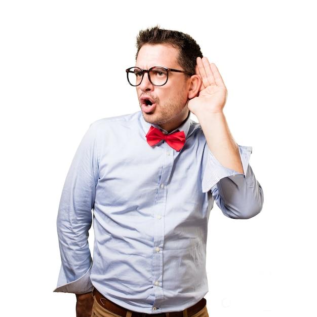 El hombre que lleva una pajarita roja. prestar atención a un ruido. Foto gratis