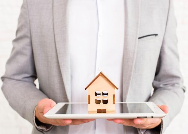 Hombre que sostiene una casa de madera en una tableta Foto gratis