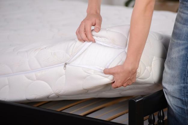 Hombre que sostiene demostraciones colchón de calidad en el dormitorio. Foto Premium