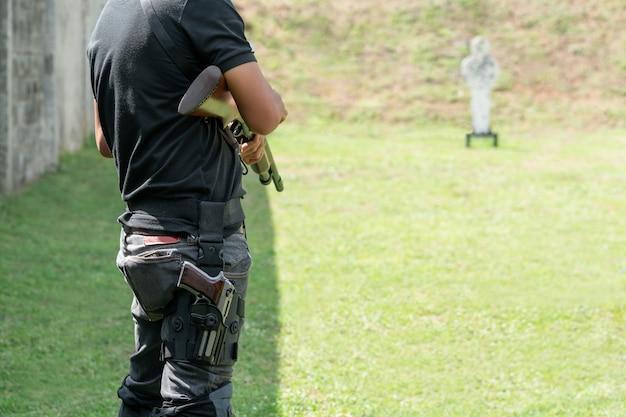 El hombre que sostiene la escopeta y lleva la pistola en la pantorrilla al frente de target en el campo de tiro. Foto Premium