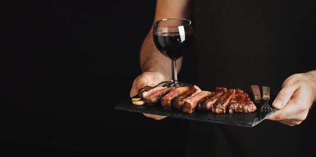 Hombre que sostiene el filete de carne de vaca asado a la parilla jugoso. Foto Premium