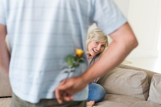 Hombre que sostiene la flor detrás con la mujer sentada en el sofá ... f7ef7fd97cb2