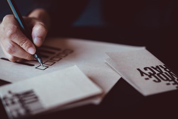 Hombre que sostiene la pluma para marcar en el papel de voto Foto Premium
