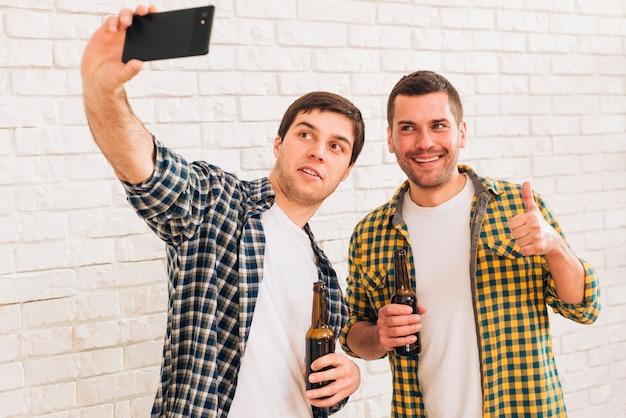 Hombre que toma selfie con su amigo en el teléfono inteligente de pie contra la pared de ladrillo blanco Foto gratis