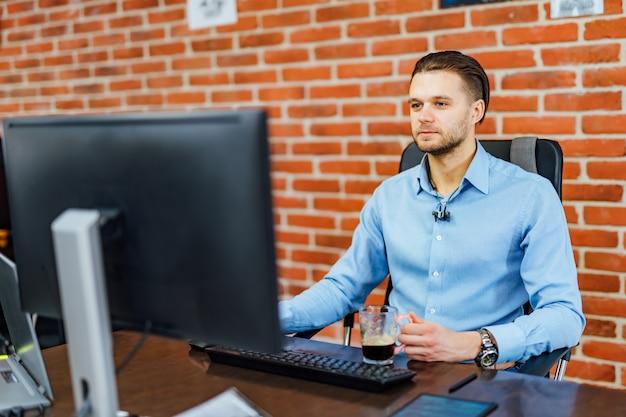 Hombre que trabaja con la computadora en la oficina de la empresa. Foto Premium