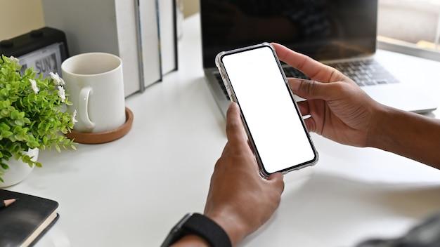 Hombre que usa el teléfono móvil de la maqueta en el escritorio de oficina con la exhibición del camino de recortes. Foto Premium