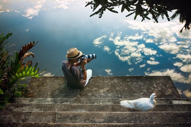 Hombre que viaja tomando una fotografía en el viejo muelle contra el hermoso cielo azul reflejo en el piso de agua Foto Premium
