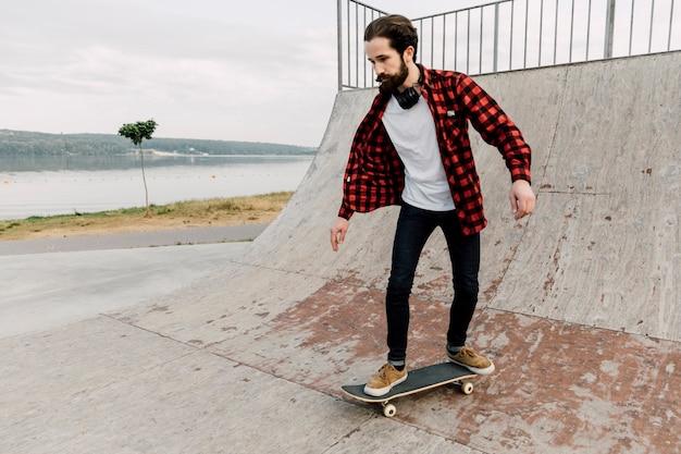 Hombre en una rampa en el skate park Foto gratis