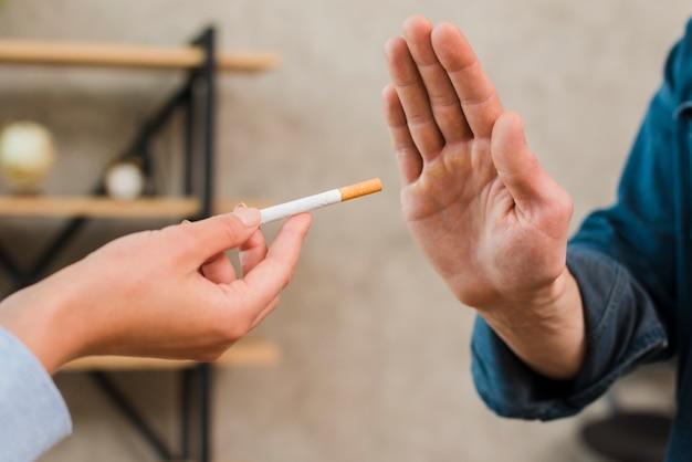 Hombre rechazando los cigarrillos ofrecidos por su colega. Foto gratis