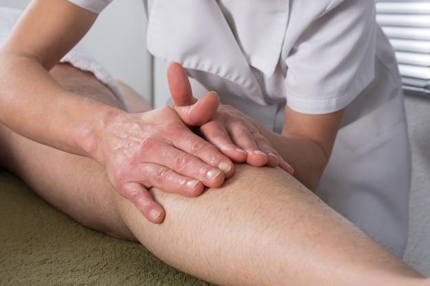 Hombre recibiendo un masaje ayurvédico en sus piernas Foto Premium