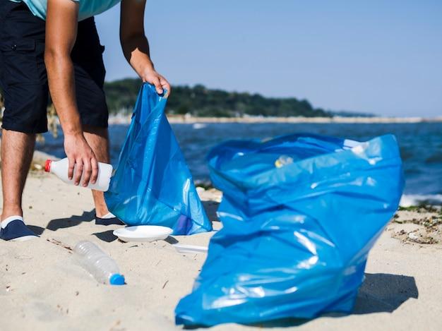 Hombre recogiendo basura plástica de la playa y poniéndola en una bolsa de basura azul Foto gratis