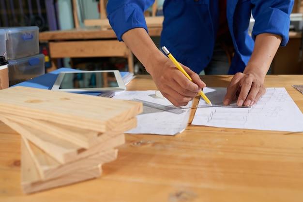 Hombre recortado con muebles de dibujo general azul en la hoja de papel Foto gratis
