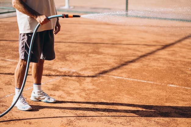 Hombre regando cancha de tenis antes del partido Foto gratis