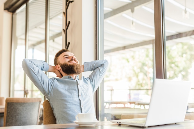 Hombre relajado que se sienta en el café con la taza de café y el ordenador portátil en el escritorio Foto Premium