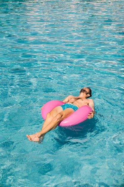 Hombre relajando en anillo flotador en piscina   Descargar Fotos gratis