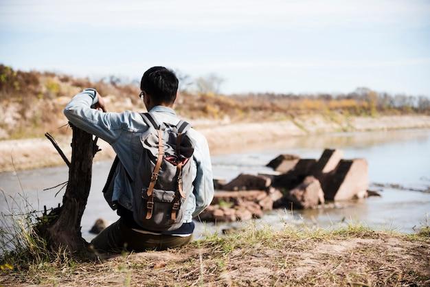 Hombre relajante cerca del lago Foto gratis