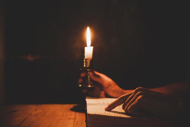 Hombre religioso sosteniendo velas encendidas y leyendo la santa biblia y orando en la iglesia Foto gratis