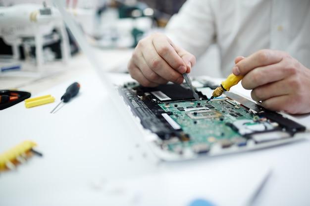 Hombre reparando la placa de circuito en la computadora portátil Foto gratis