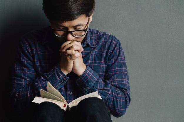 Hombre rezando en la sagrada biblia en la mañana. mano de muchacho adolescente con biblia rezando, Foto Premium