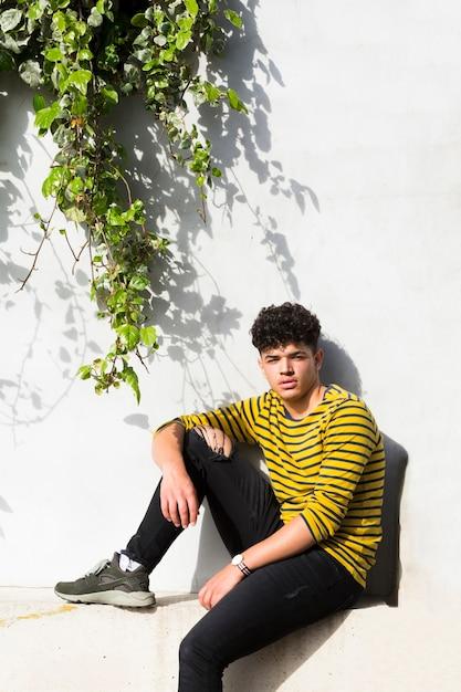 Hombre rizado étnico sentado cerca de la pared con plantas verdes Foto gratis