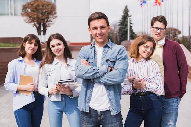 Hombre rodeado de estudiantes inteligentes con libros mirando a cámara Foto gratis