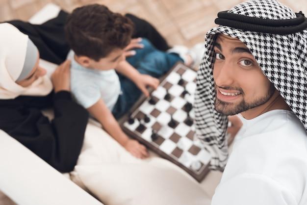 Un hombre en ropa árabe juega al ajedrez con un niño pequeño. Foto Premium
