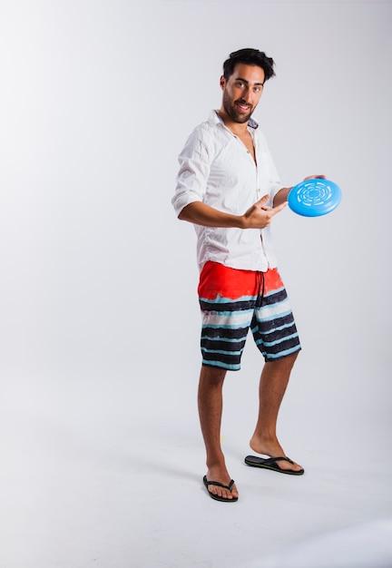Hombre en ropa de verano mostrando frisbee Foto gratis