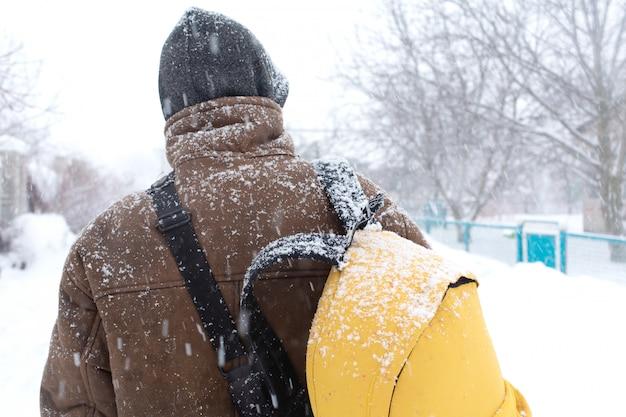 Un hombre rústico camina por la calle en invierno con una mochila amarilla. tormenta de nieve Foto Premium