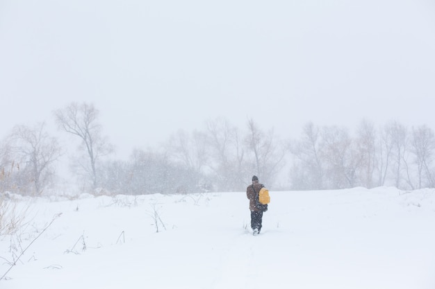 Un hombre rústico camina por la calle en invierno con una mochila amarilla. ventisca de nieve. Foto Premium