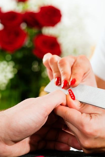 Hombre en salón de manicura recibiendo manicura Foto Premium