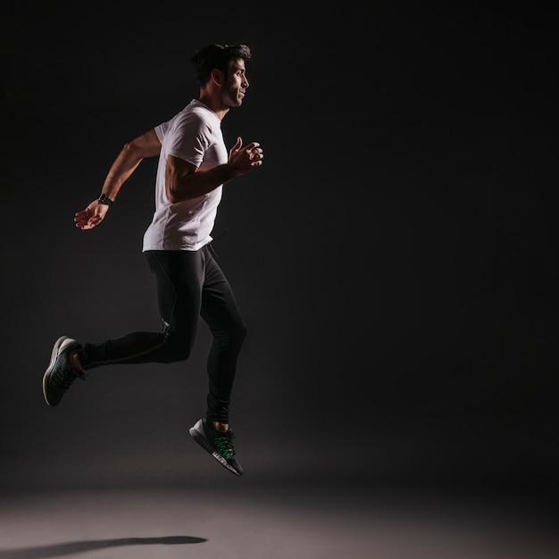 Hombre saltando sobre fondo oscuro Foto gratis