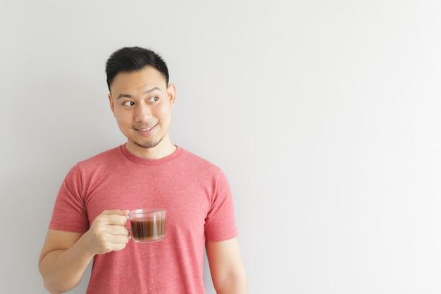 El hombre sano feliz en camiseta roja bebe el café o la bebida asiática de las hierbas. Foto Premium