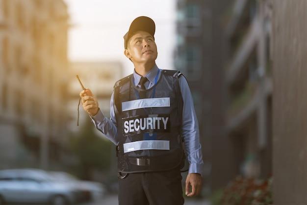 Hombre de seguridad permanente afuera usando radio portátil Foto Premium