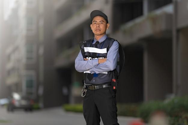 Hombre de seguridad permanente al aire libre cerca del gran edificio Foto Premium