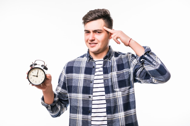 El hombre señala estrictamente el despertador aislado en el estudio en la pared blanca Foto gratis