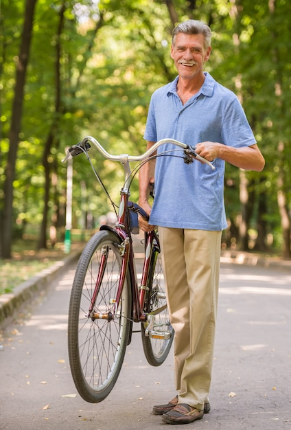 Hombre senior alegre con bicicleta en el parque. Foto Premium