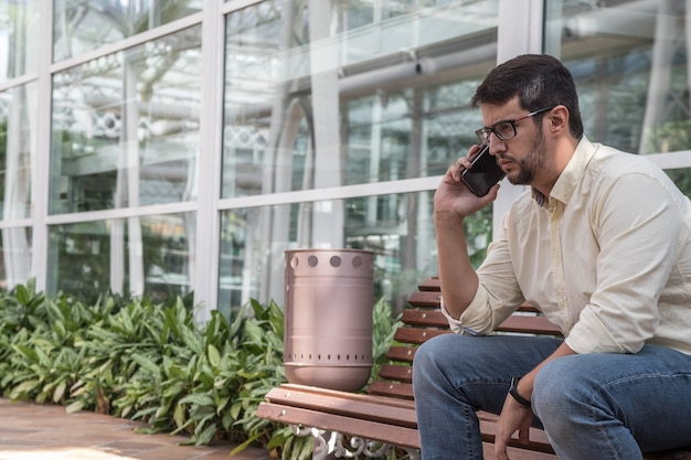Hombre sentado en un banco hablando por teléfono Foto Premium