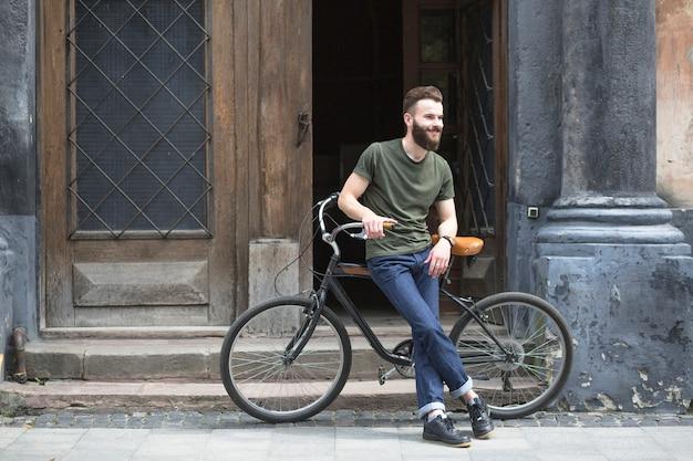 Hombre sentado en bicicleta frente a una puerta abierta Foto gratis