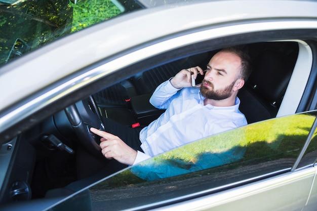 f6e0a3cd8a Hombre sentado en el coche hablando por teléfono inteligente ...