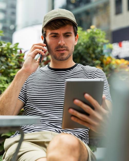 Hombre sentado mientras habla por teléfono Foto gratis