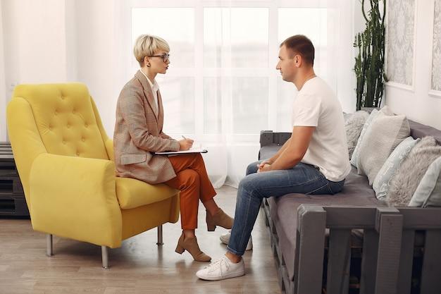 Hombre sentado en la oficina del psicólogo y hablando sobre problemas Foto gratis