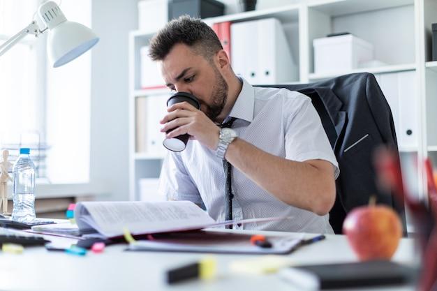 Un hombre está sentado en la oficina, tomando café y trabajando con documentos. Foto Premium