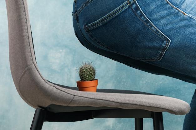 Hombre sentado en una silla con cactus. hemorroides Foto Premium
